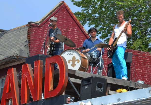 Three musicians are playing on a rooftop, two guitar players and a drummer. They are on top of the Fairland grocery store in Kensington