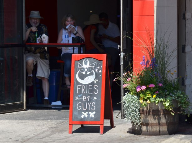 Chalkboard sign outside a restaurant that says Fries b 4 guys. Two people are inside the restaurant, sitting at a table and eating