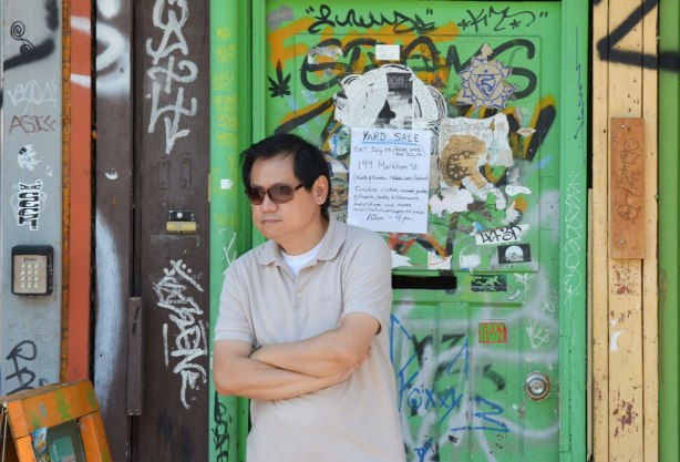 A man is standing in front of a green door that is covered with stickers, graffiti and bits of old posters