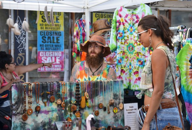 A man with a bushy beard and pointy brown hat is sitting at a table selling things like necklaces and tie dyed shirts