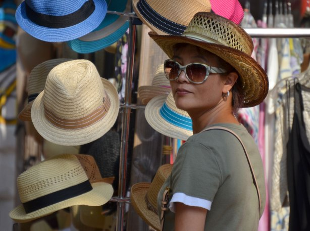 A woman is wearing a hat and sunglasses. She is beside a rack of many straw hats with different coloured bands.