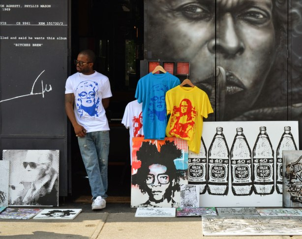 A man is wearing a T-shirt with a picture of Marilyn Munroe with sunglasses on it. He is trying to sell T-shirts and other works of art outside on the sidewalk. Beside him is a street art painting of a man's face, with his finger in front of his lips.