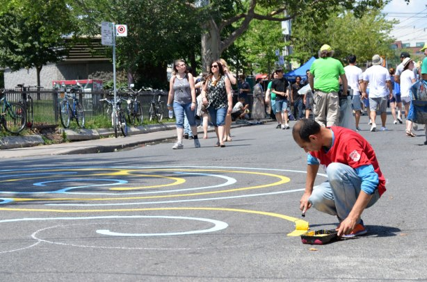 A man is painting a circular maze on a street