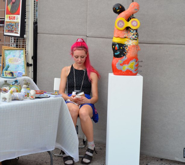 A woman with long bright pink hair sits beside a table of art wortks for sale. Beside her is white pedestal with a brightly coloured abstract sculpture on it