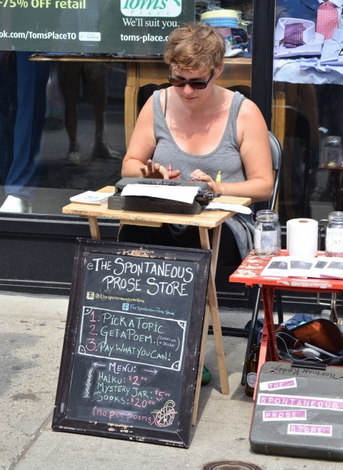 A woman is typing on an old typewriter at an outdoor event, Pedestrian SUnday at Kensington Market. She is the Spontaneous PRose Shop. Pay her and she'll compose haiku, poetry or stories for you.