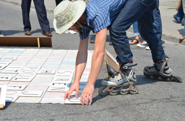 A man plays scrabble outdoors on the street while wearing roller blades