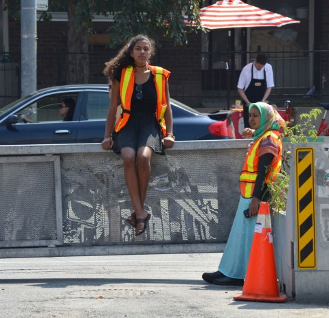 Two women in orange and yellow safety vests. One is sitting on a waist high barrier to keep cars off the street while the other woman is standing and leaning against it.