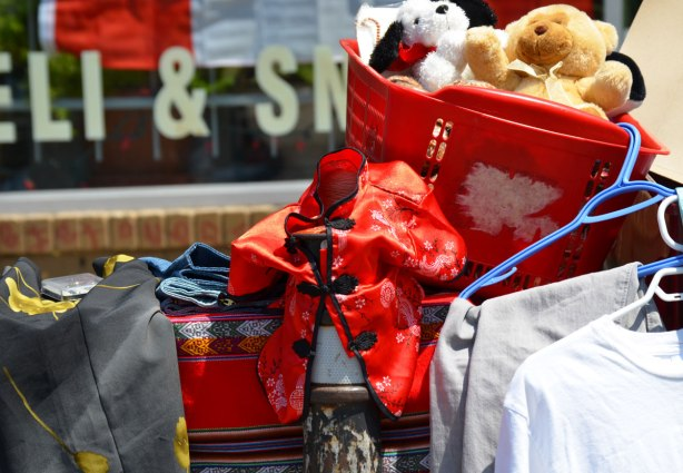 An assortment of things for sale on a table including a basket of stuffed animals, some shirts on hangers and a childs red Chinese jacket.