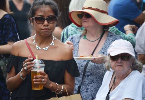 three women at an outdoor event. One is wearing sunglasses and a silver necklace. She is holding a cold drink in her hands. The other two women are older and are wearing hats.