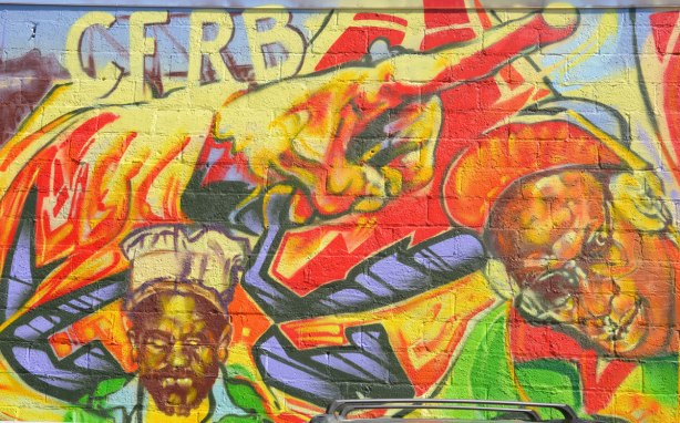 Part of a very colourful mural depicting various reggae musicians - A large hand with a finger pointing to the right with the letters C F R B above it. Two musicians are also in the picture.