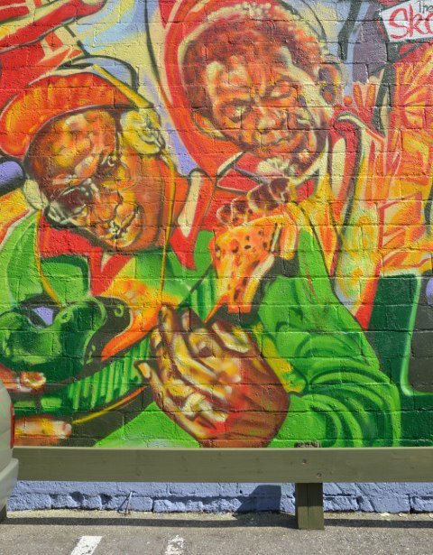 Part of a very colourful mural depicting various reggae musicians - A man wearing headphones and a baseball cap is playing a guitar.