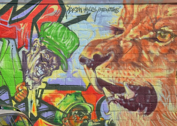 Part of a very colourful mural depicting various reggae musicians - a black man in a green hat, a lion's face and the words, Adrian Hayles production
