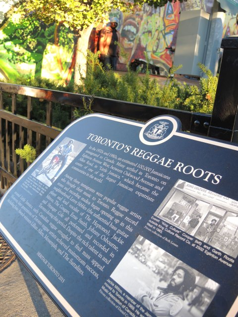 "plaque with the title ""Toronto's Reggae Roots"" with three photos as well as a story of Jamaican immigrants to Toronto and the story of reggae music in Toronto"