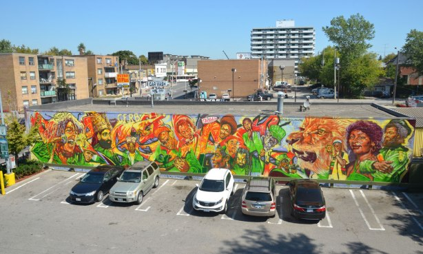 View of a 1200 square foot mural by Adrian Hayles that depicts many different reggae musicians. This photo was taken from the second floor of the building next door so the camera is looking down across the parking lot towards the mural. Eglinton Avenue is seen behind the mural.