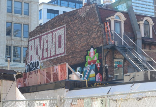 the demolition of a building has made it easier to see some street art and signs on the upper part of the side of a building. One is the word Alveno (or maybe Alvend) written in large block letters. Another is a colourful geometric design.