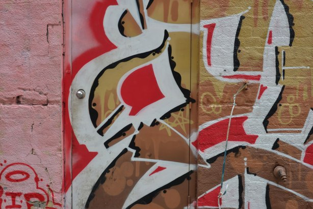 door in an alley is covered with a street art piece in golds, reds and white