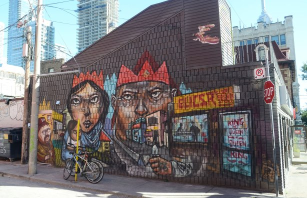 a mural by artist elicsr on the side of a convenience store. The side of the building faces an alley. A large man and woman are in the mural and they are wearing red crowns. The woman has a young girl sitting in her arms. There is another man in the mural, he covers the back entrance to the building.
