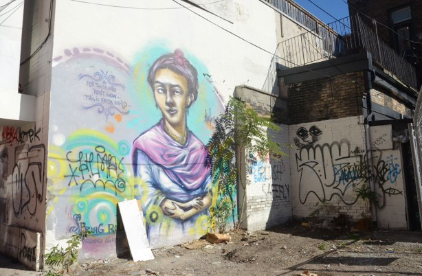 A painting of Frida Kahlo on a wall. Larger than life size. She has a purple shawl around her shoulders.