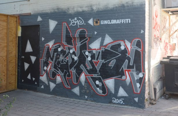A street art piece in grey tones with some black and white, by gino.graffiti (that is how he has signed it). Done in 2015. In an alley beside a black metal door.