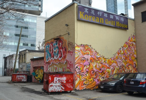 The back of the Korean Grill House restaurant, and the alley that its in. There is lots of street art on it. Two red garbage bins are also in the picture and they too have graffiti on them.