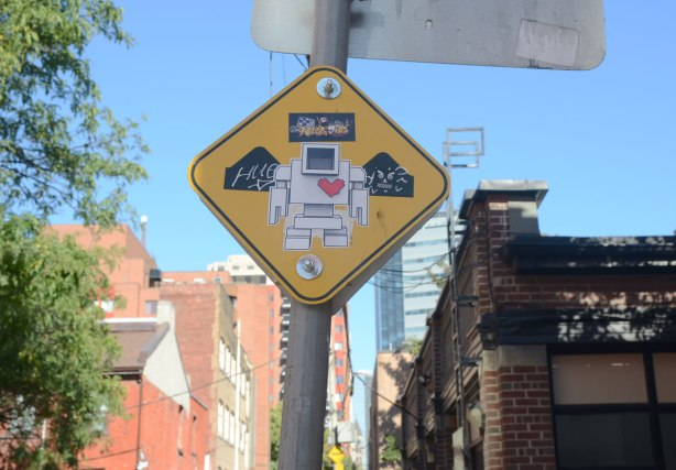 A yellow sign warning of speed bumps in the lane has a big lovebot sticker in the middle of it. Buildings in the background.