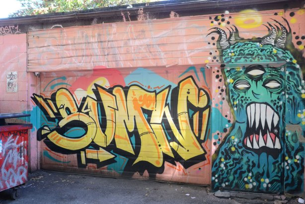 Street art on an alley garage that covers the whole of the front including garage door and entranceway. On the entrance door is a greenish horned three eyed, big teeth monster