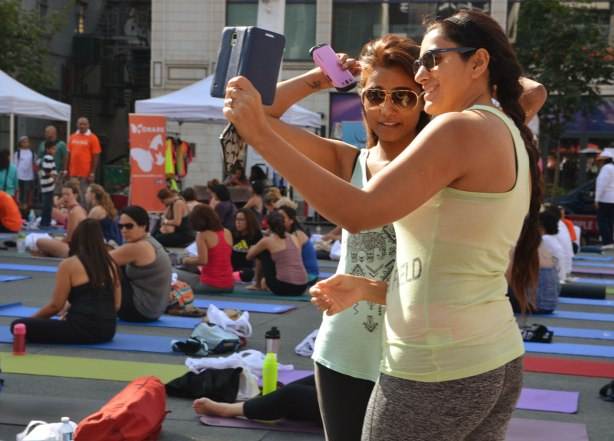 Two women taking a selfie at a yogathon, they are standing. Other people around them are sitting on mats, waiting for the event to begin.