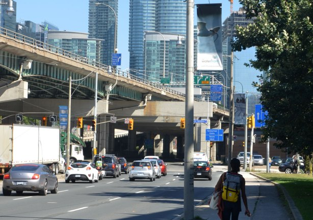 A woman is walking on a sidewalk, away from the camera, beside the Lakeshore Blvd in Toronto. There are a few cars on the road. There are skyscrapers in the background. The elevated highway, the Gardiner Expressway, is also in the picture.