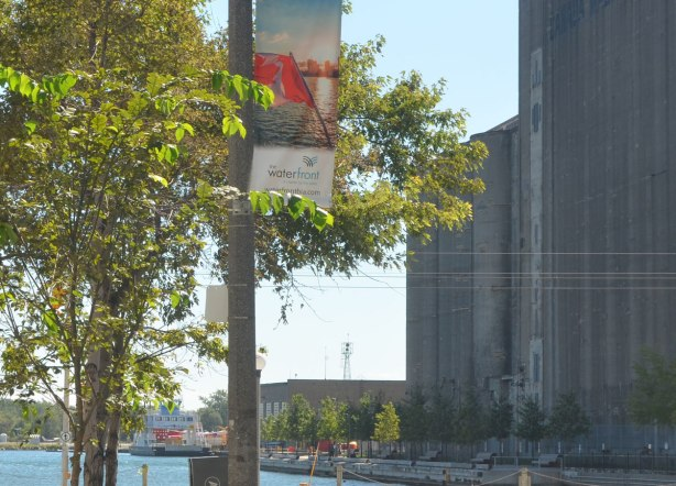 looking towards the waterfront. A banner with a picture of the Canadian flag is on a post by a tree in the foreground. The old silos for Canada Malting Company are in the background as is a boat moored beside the silos.