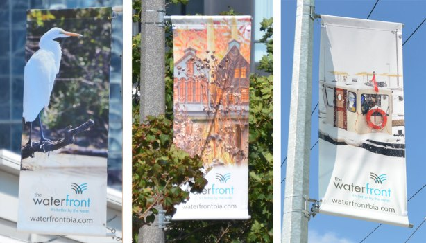 Three pictures in one. Each of the pictures is of a banner hanging from a pole outside. On the left is a picture of seagull, in the middle is a picture of two houses and on the right is a winter waterfront scene