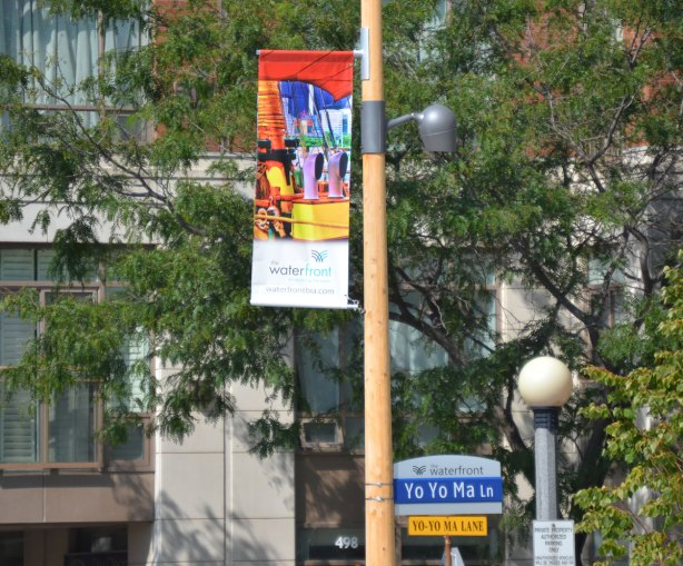A pole with a vinyl banner with a colourful picture of boats. Also on the pole is a street sign that says Yo Yo Ma Lane