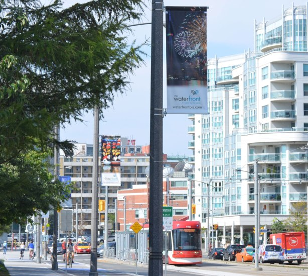 Looking west on Queens Quay towards Bathurst street. New TTC streetcar is in the photo as well as a number of condos and other buildings on the north side of the street