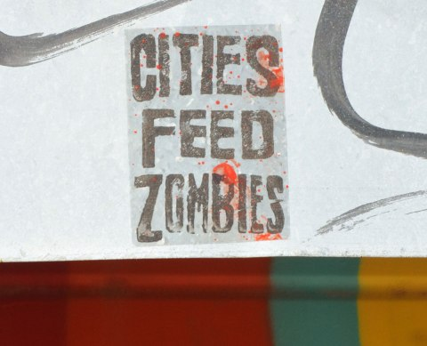 a stenciled sign that says Citied Feed Zombies