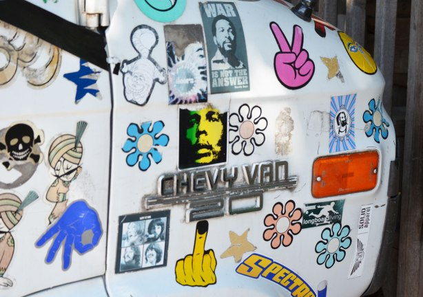 Front panel of a white chevy van that is covered with stickers, a pink hand giving a peace sign, daisies, anti-war stickers