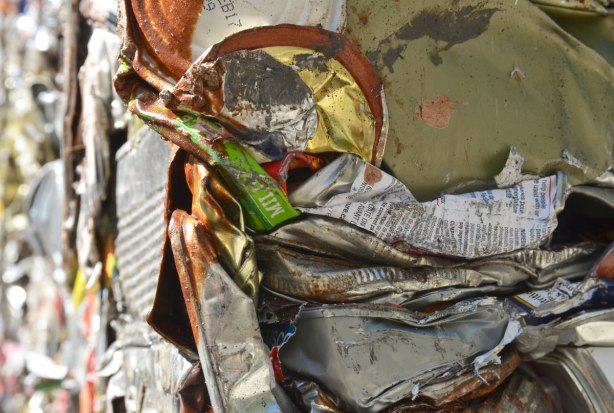 A bundle of old rusty tin cans that have been crushed and pack into large bundles ready to be recycled.