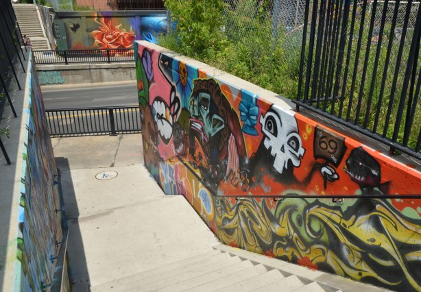 part of a larger mural painted on the side of an underpass - also painted on the sides of the stairwell that access the path that crosses over the bridge