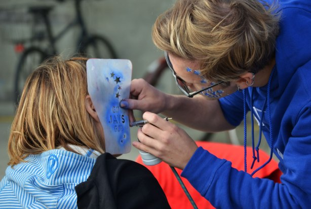 Before a Blue Jays baseball game at the ROgers Centre - a woman gets the words Go Jays Go painted onto her cheek in blue and white paint