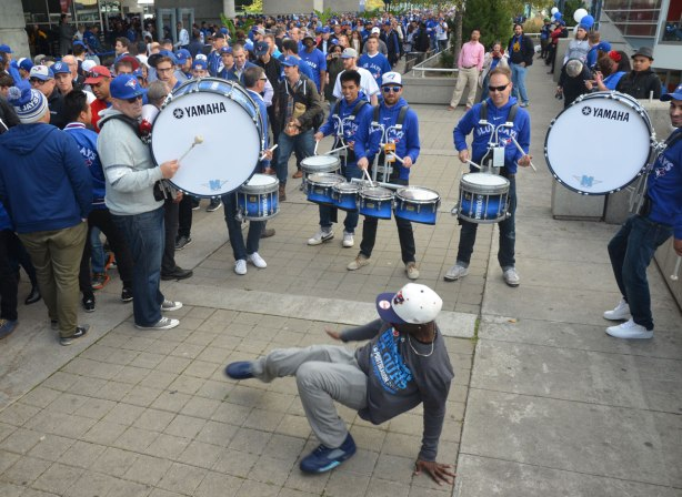 Before a Blue Jays baseball game at the ROgers Centre - a young man wearing a Jays grey T-shirt break dances in front of a5 man drum band who are all wearing blue Blue Jays T-shirts. There are many fans watching them play.