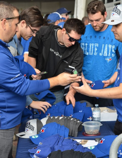 Before a Blue Jays baseball game at the ROgers Centre - a group of men buy baseball caps from a vendor outside the stadium.