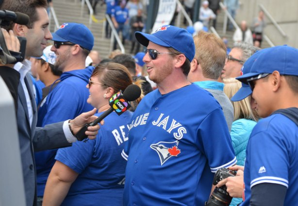 Before a Blue Jays baseball game at the ROgers Centre - a man in Blue Jays shirt and cap is being interviewed by CHCH TV
