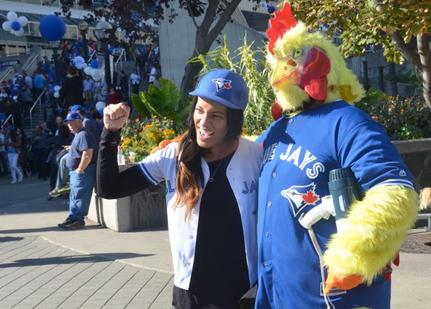 Before a Blue Jays baseball game at the ROgers Centre - a young woman poses with a man dressed in a chicken costume and a Blue Jays T-shirt
