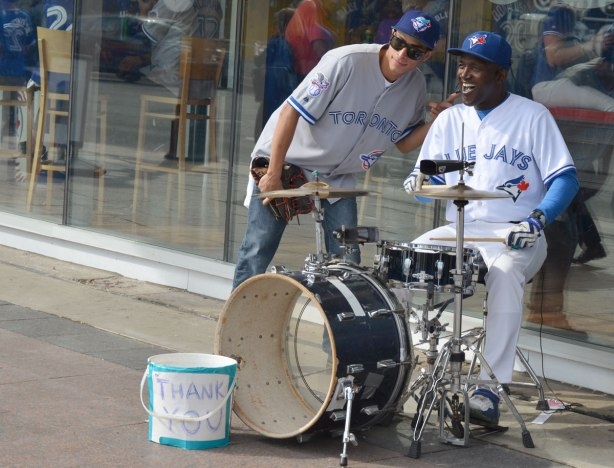 A man wearing a white Blue Jays uniform plays the drums while an onlooker poses beside him for a picture.