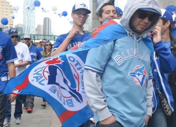 young man wearing Toronto Blue Jays light blue jersey, and he's wearing a  blue jays flag as a cape that is billowing out from behind him.  Other young men are around him, on their way to baseball game.
