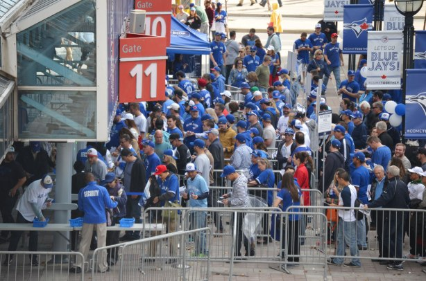 Before a Blue Jays baseball game at the ROgers Centre - security guards checking the people entering through gates 10 and 11 at the Rogers Centre for a baseball game