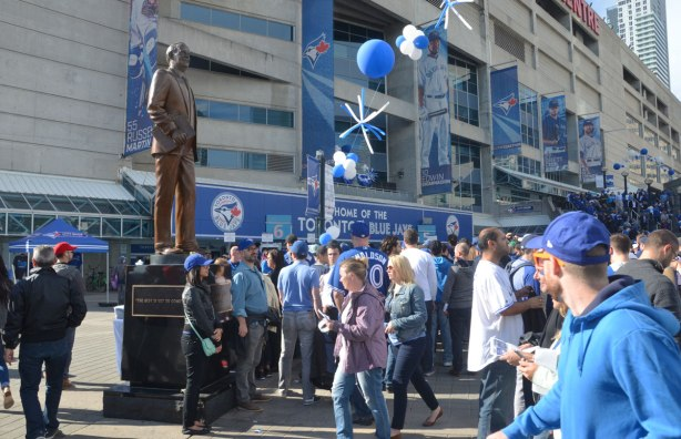 Before a Blue Jays baseball game at the ROgers Centre - the crowd waits in line to get into the stadium, with a statue of Ted Rogers standing over the people