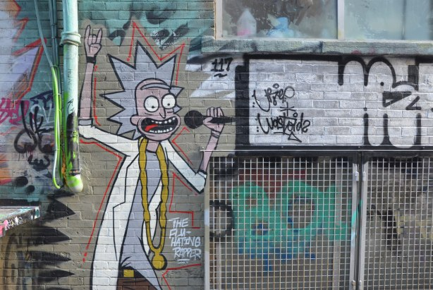 A character in a white lab coat and with spikey grey hair, street art painting. He's hold a microphone to his mouth. The words say Flu Hating Rapper
