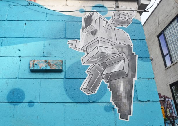 large wheatpaste lovebot on a wall that's been painted sky blue. 3D lovebot looks like he's running or jumping.
