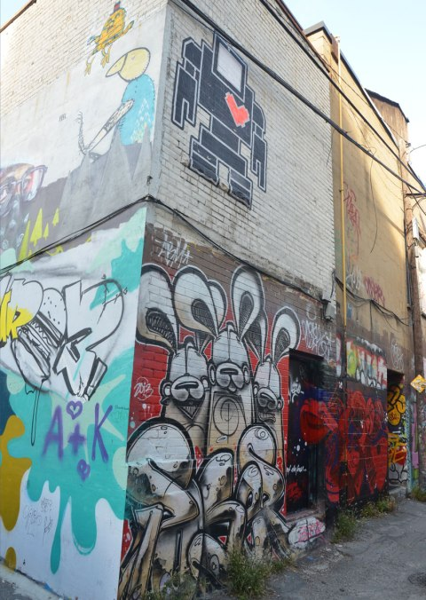 The corner of a two storey building in Graffiti Alley, photo taken so that both sides of the building are visible. On one side is a group of poser bunnies in brown and white with red background on the lower flooor and a blck lovebot with red heart on the upper floor. On the other side of the corner is a Uber5000 bird above and something that's been tagged over on the bottom.