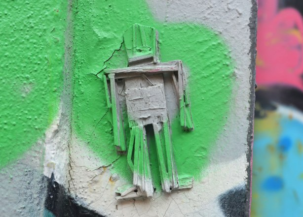 Stickman on a wall with green and grey spray paint on top of him and around him