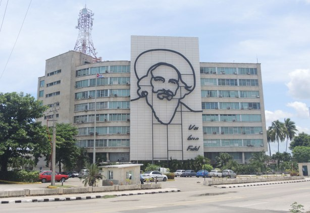 A multi storey building with a line drawing Fidel Castro's face as well as the words Vas bien Fidel